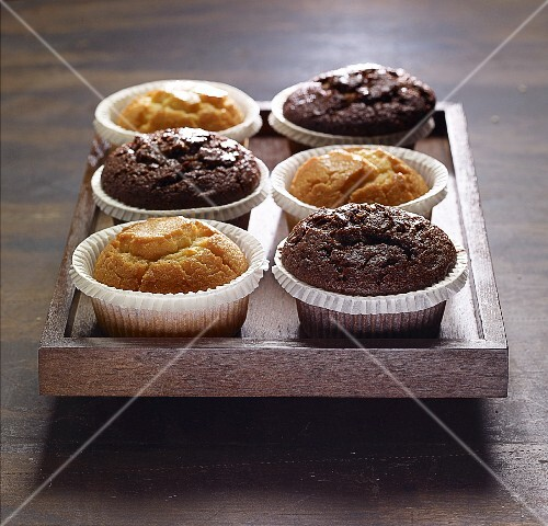 Various muffins on a wooden tray