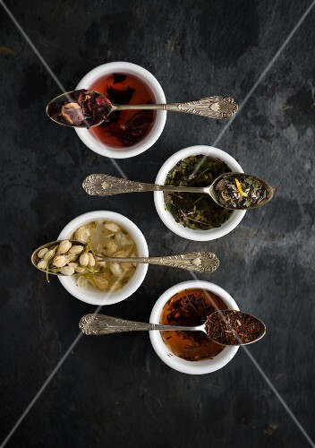 Various types of tea on vintage spoons over bowls (seen from above)