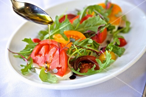 A heirloom tomato salad with rocket, balsamic vinegar and olive oil