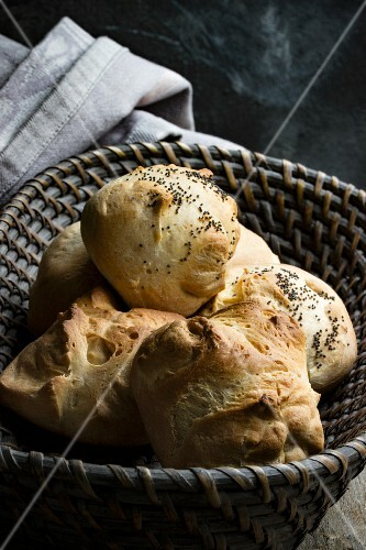 Poppyseed rolls in a grey bread basket with a fabric napkin