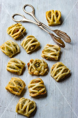 Puff pastries filled with herb and cream cheese with a pair of pastry tongs