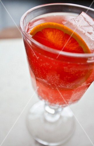 A glass of blood orange soda with citrus slices and ice cubes