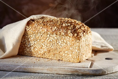 A steaming loaf of spelt-chia bread on a chopping board