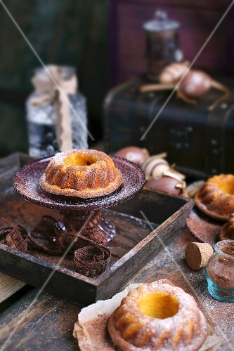 A mini orange and pumpkin Bundt cake on a cake stand on a wooden table