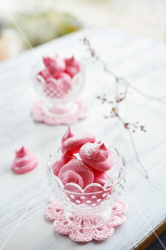 Pink meringues in glass bowls on an old table