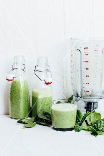 Green smoothies, spinach leaves and a blender