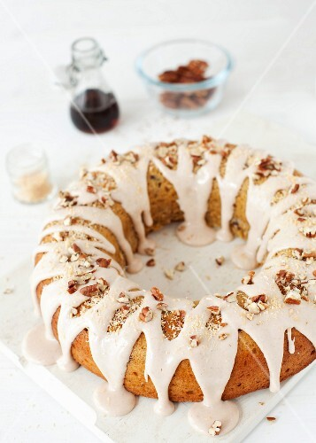 An iced ring shaped sponge cake with nuts and roasted coconut