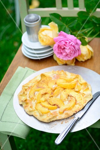 Galette with nectarines and peaches on a chair outside