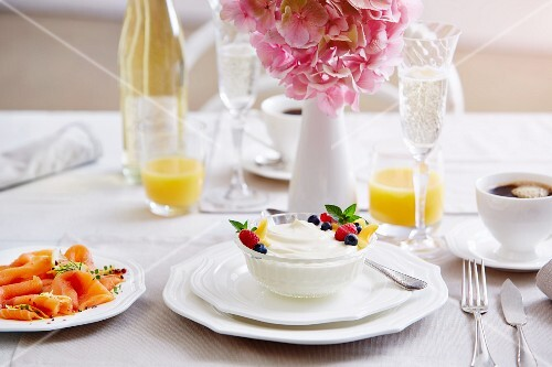 A breakfast table with yoghurt, salmon, coffee, Prosecco and orange juice