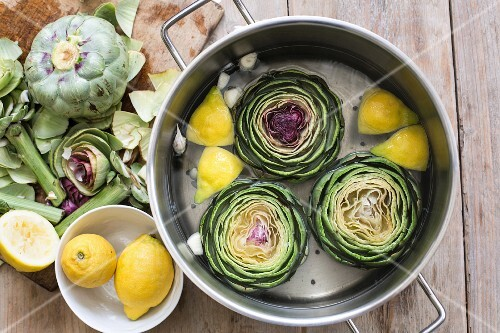 Artichokes with water, lemon and garlic in a pot