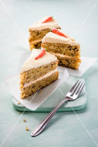 Three slices of carrot cake with a fork