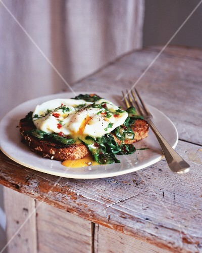 A poached egg with spinach on toast