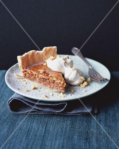 A slice of nut and caramel pie with cream