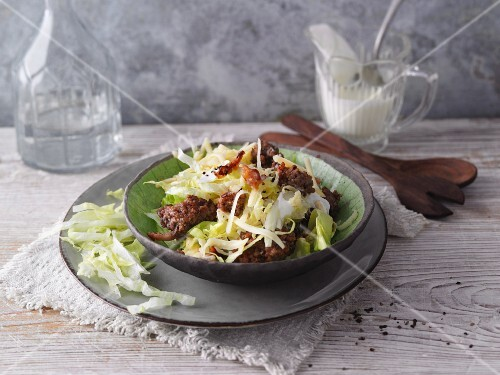 Iceberg lettuce with fried minced meat and bacon