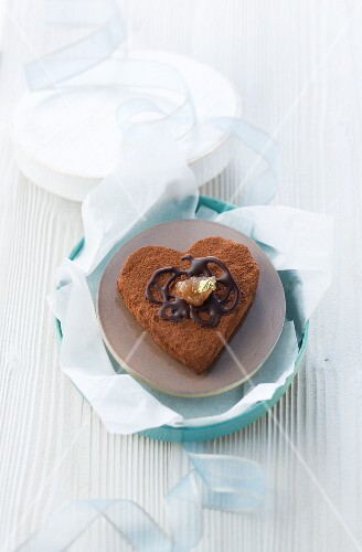 A heart-shaped chocolate cake with edible chestnuts as a gift