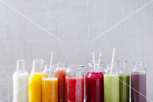 Various smoothies in glass bottles
