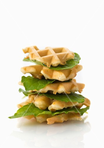 A stack of vegan waffles with lettuce leaves on a white surface