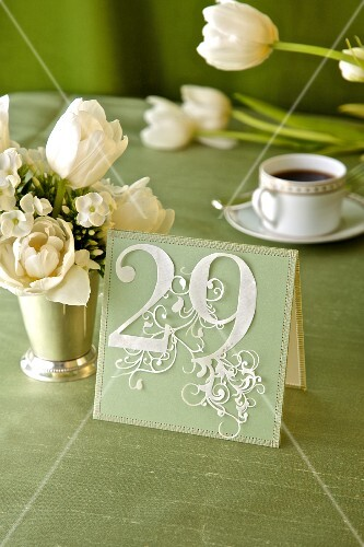 Decorative place card with number 29 on festive table