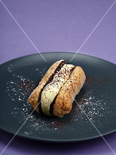 A sponge finger filled with mascarpone and chocolate sauce