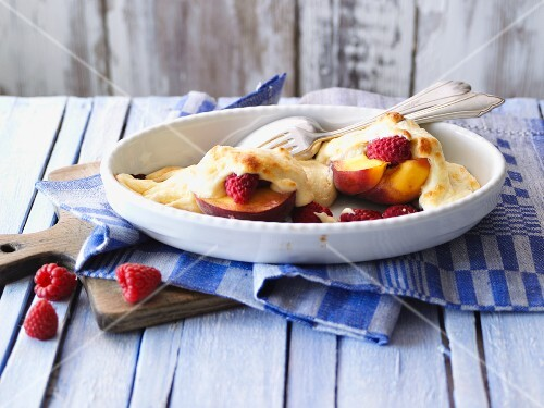 Baked peaches with raspberries in a baking dish