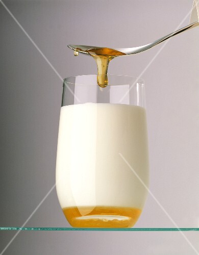 Honey running from a spoon into a glass of milk (1)