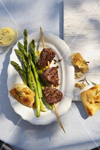 A beef kebabs with green asparagus and unleavened bread