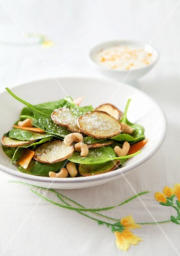 A spinach salad with potatoes and cashew nuts