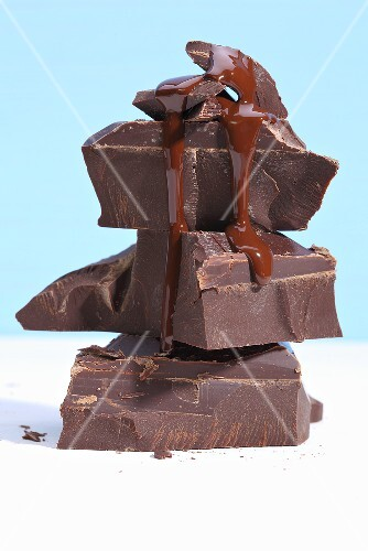 Liquid chocolate dripping down a stack of chocolate pieces