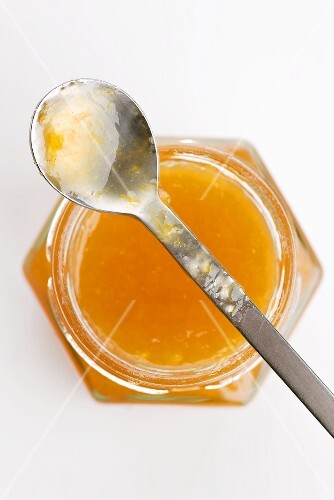 Apricot jam in a jar with a spoon (seen from above)