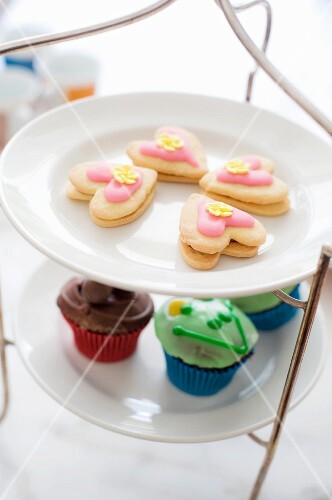 Cake stand with heart-shaped biscuits and cupcakes