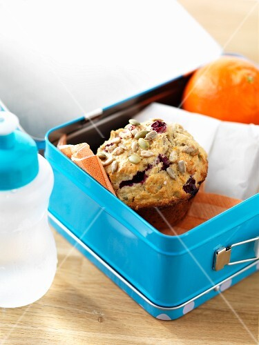 A cranberry muffin and an orange in a lunch box