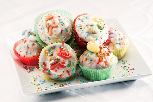 Muffins with icing, colourful sprinkles and sugar ornaments