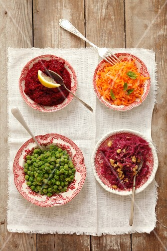 Four salads: red cabbage with walnuts, peas with dill, butter and breadcrumbs, carrots with apple, grated beetroot with horseradish
