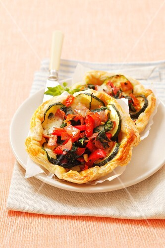 Puff pastry tartlets topped with courgettes, spinach, pepper and mozzarella
