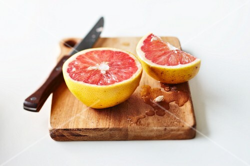 Cut pink grapefruit on chopping board