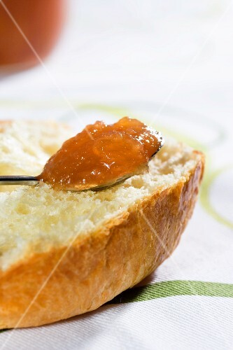 A spoonful of peach jam on a slice of brioche