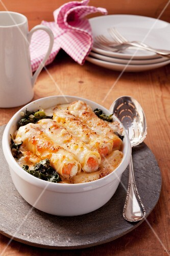 Cannelloni filled with salmon and ricotta on a bed of spinach