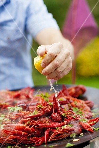 Squeezing lemon juice onto barbecue crayfish