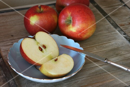 Red apples, a fruit knife, an apple half and a quarter