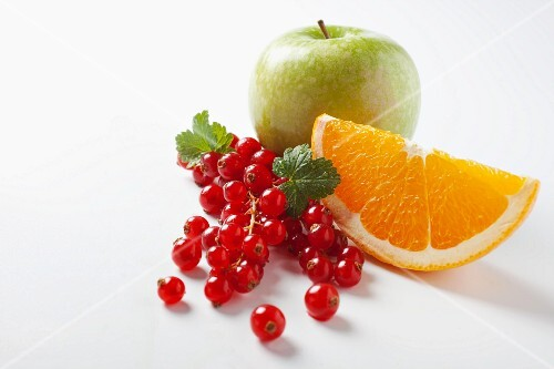 Redcurrants, an orange wedge and an apple