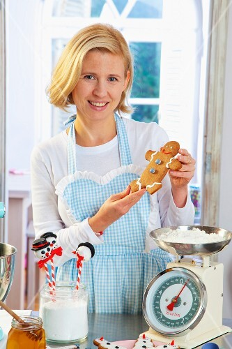A woman with a gingerbread man and ingredients in a kitchen