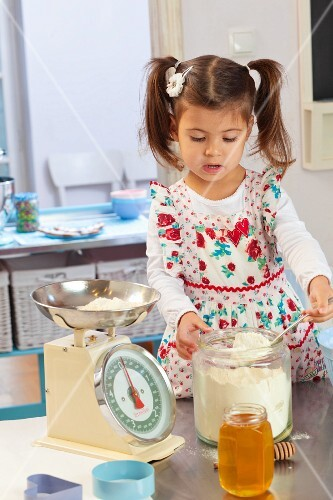 A little girl weighing ingredients in a kitchen
