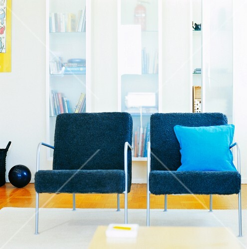 Two blue upholstered chairs in a living room