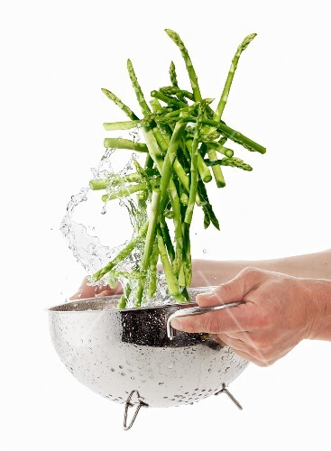 Washing green asparagus in a colander