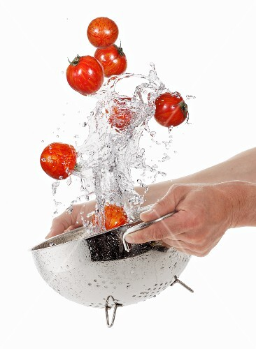 Washing tiger tomatoes in a colander