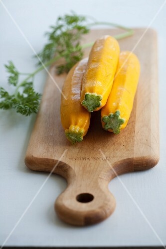 Three yellow courgettes on a chopping board