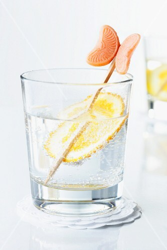 An orange slice and a stick in a glass of water