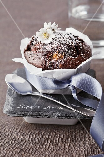 A chocolate muffin decorated with candied daises