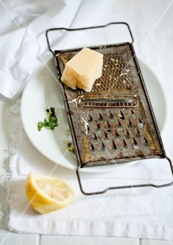 A piece of parmesan on a rusty grater