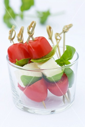 Tomato and mozzarella mini skewers with basil leaves